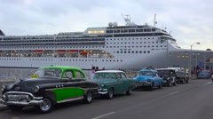 Massive cruise ships dock at Havana harbor, Cuba with classic old cars in the Stock Footage