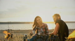 Couple in love having drinks while sitting at the camp tent at sunset Stock Footage