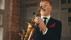 Saxophonist in dinner jacket play on golden saxophone at stage. Jazz vocalist Stock Footage