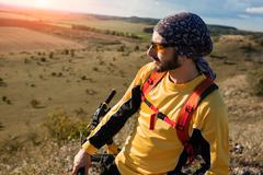 Mountain Bike cyclist riding single track above sunset valley Stock Photos