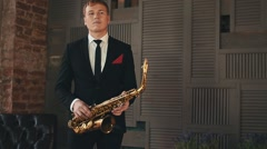 Saxophonist in dinner jacket dance with golden saxophone at stage. Jazz artist Stock Footage