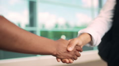 Close up view of colleagues' handshake, business centre background. Slow motion Stock Footage