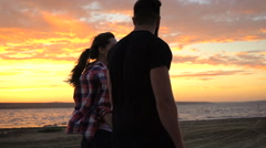 Couple in love walking on beach at sunset holding hands Stock Footage