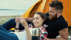 Couple in love talking while relaxing at the camp tent Stock Footage