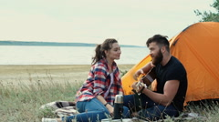 Man playing guitar for his girlfriend while sitting at th Stock Footage