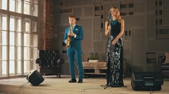 Jazz vocalist in glare dress, saxophonist in blue suit prepare perform on stage Stock Footage