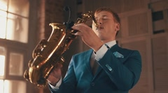 Saxophonist in blue suit play jazz on golden saxophone with microphone. Elegance Stock Footage