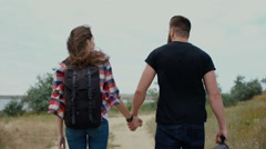 Couple with backpack walking along the road Stock Footage
