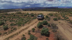 Following SUV Down Rugged Desert Road to Campsite Stock Footage