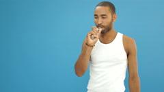 Man in white t-shirt smokes a vape e-cigarette Stock Footage