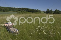 Mann ruht auf de Wiese Stock Photos