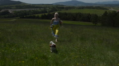 Lady is Running with Her Dog over a Field Arkistovideo