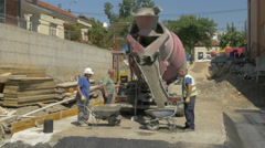 Workers pouring concrete in wheelbarrows from mixer truck,wide angle by Sheyno. Stock Footage