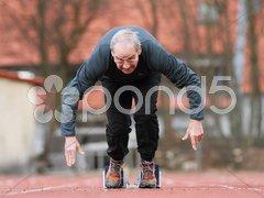 Senior beim Sprintstart Stock Photos