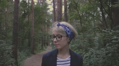 Beautiful girl in a forest walking toward the camera Stock Footage