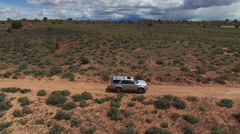 Orbiting SUV Driving Down Rugged Desert Road Stock Footage
