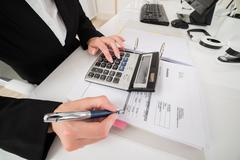 Female Accountant Calculating Data With Calculator At Desk Stock Photos