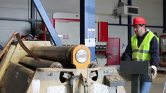 Worker bending metal on hydraulic machine with three rollers Stock Footage