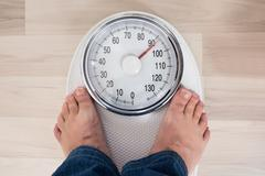 Low Section Of A Person Standing On Weighing Scale Stock Photos