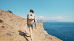 Slow motion of a young female walking a trail on the seashore cliff Stock Footage