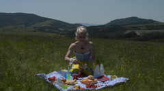 Lady on Picnic Tearing apart Bread and Muffin Stock Footage