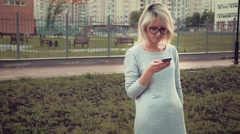 Happy young woman standing in the park area among buldings using her smartphone Stock Footage