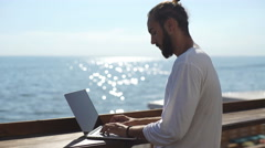 Successful businessman uses a laptop in a cafe outdoors on sea background Stock Footage