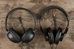 Two headphones and the cord symbolic of a love for music on an antique wooden Stock Photos