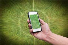 Hand holding smartphone with green field on screen Stock Photos