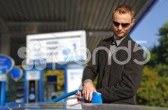 Junger Mann mit Cabrio an  Tankstelle Stock Photos
