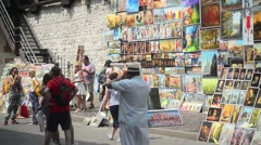 Passers buy Paintings of Street artists and Souvenirs - old Krakow Stock Footage