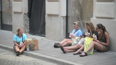 Girls Tourists Eat Street Food Sitting in the Square in a Crowded Place - Krakow Stock Footage