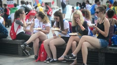 Women Tourists Eat Street Food Sitting in the Square in a Crowded Place - Krakow Stock Footage