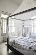 Canopy bed with mosquito netting Stock Photos