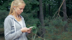 Attractive blond girl using a smartphone and turning on the music Stock Footage