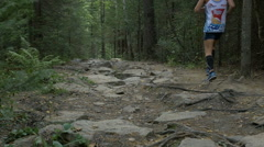 Group of young runners men run on a mountain trail in forest Stock Footage