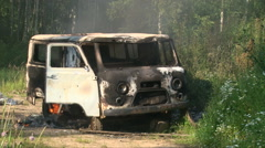 Old burning car emitting in smoke empty summer field Stock Footage