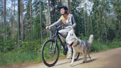 Active girl cycling with her dog next to her on the forest road Stock Footage