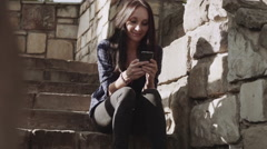 Beautiful young woman uses mobile phone while sitting on stairs during sunset. Stock Footage
