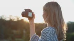 Beautiful Young Female Photographer Taking Pictures 8 at sunset Stock Footage