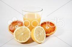 Orangensaft im Glas und Zitrusfrüchte Stock Photos