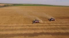 Aerial shot, camera flying round of two harvester moving on golden field and Stock Footage