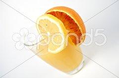 Glas mit Orangensaft und Zitronenscheibe Stock Photos