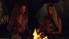 Friends speaking, smiling, playing on instruments, sitting near bonfire at night Stock Footage