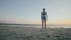 Young woman with a slender figure is engaged in gymnastics at sunrise. Slow Stock Footage