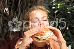 Woman eating cheeseburger Stock Photos