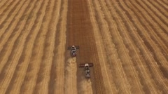 Aerial top view of two modern harvesters moving on a field with narrow band of Stock Footage