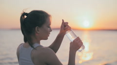 Young Athlete girl drinking water after fitness run, jogger training at summer Stock Footage