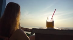 Woman Relax in a Cafe with a Cocktail Against os the Sunset. Slow Motion Stock Footage