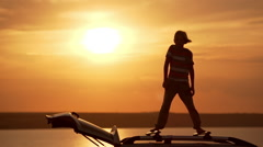 Silhouette of young handsome boy rejoicing, dancing on roof of car in field at Stock Footage